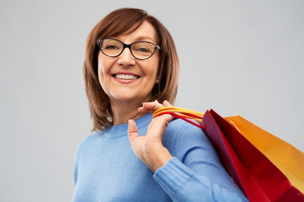 smiling senior woman in glasses with shopping bags over grey background