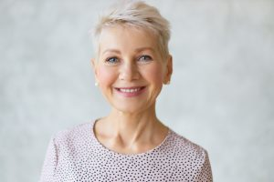 Close up image of good looking beautiful mature blonde female with blue eyes, elegant make upand pixie hairstyle smiling at camera, having confident happy facial expression, being in good mood