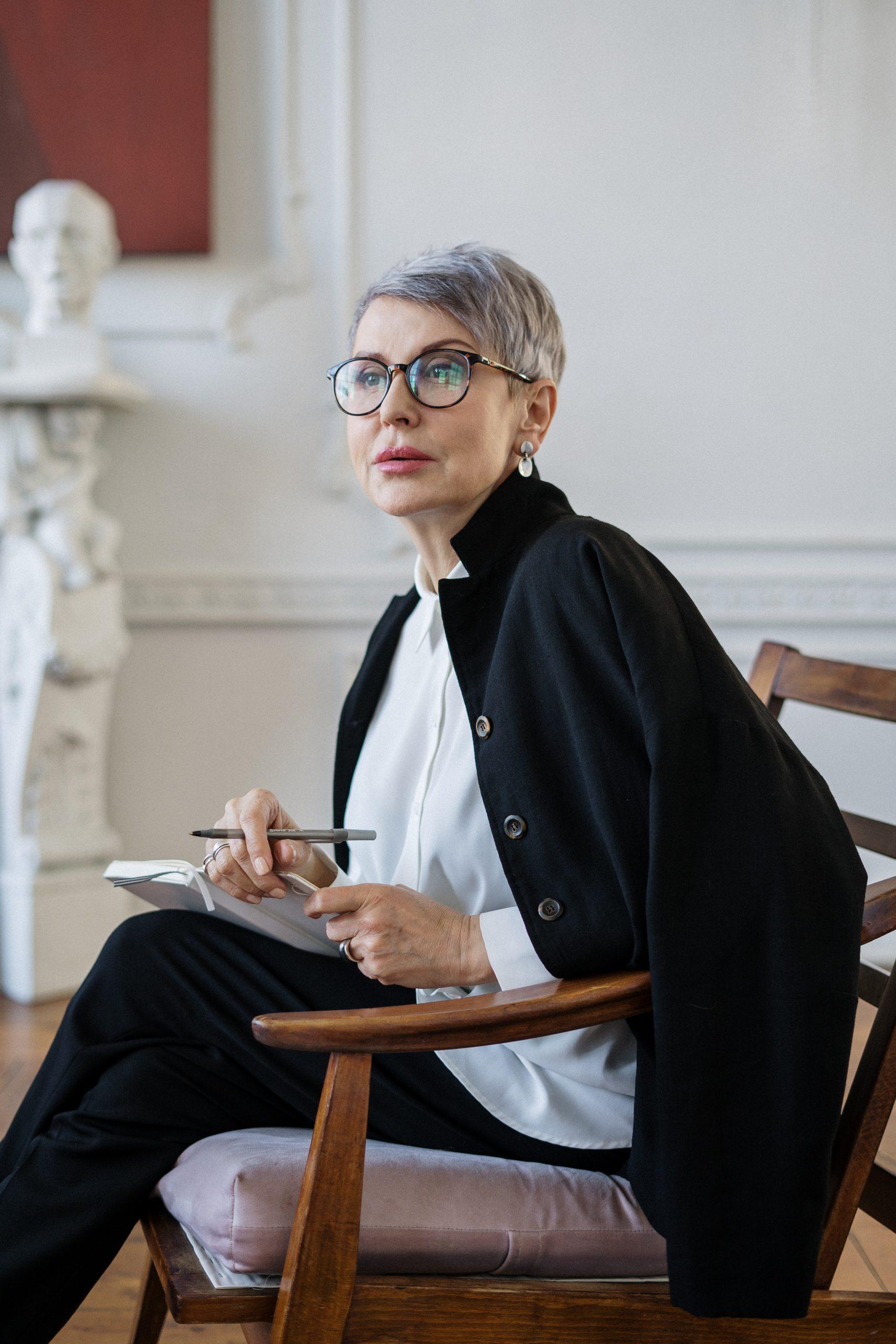 woman-in-black-blazer-sitting-on-brown-wooden-chair